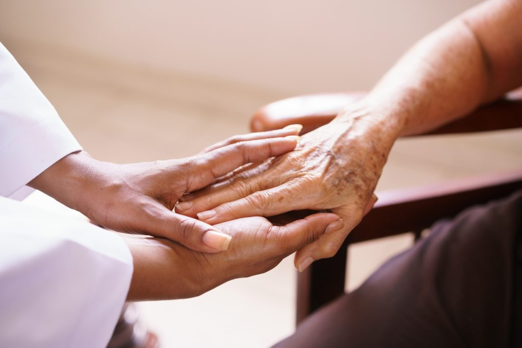 Two hands joining one from a care giver the other from someone receiving care