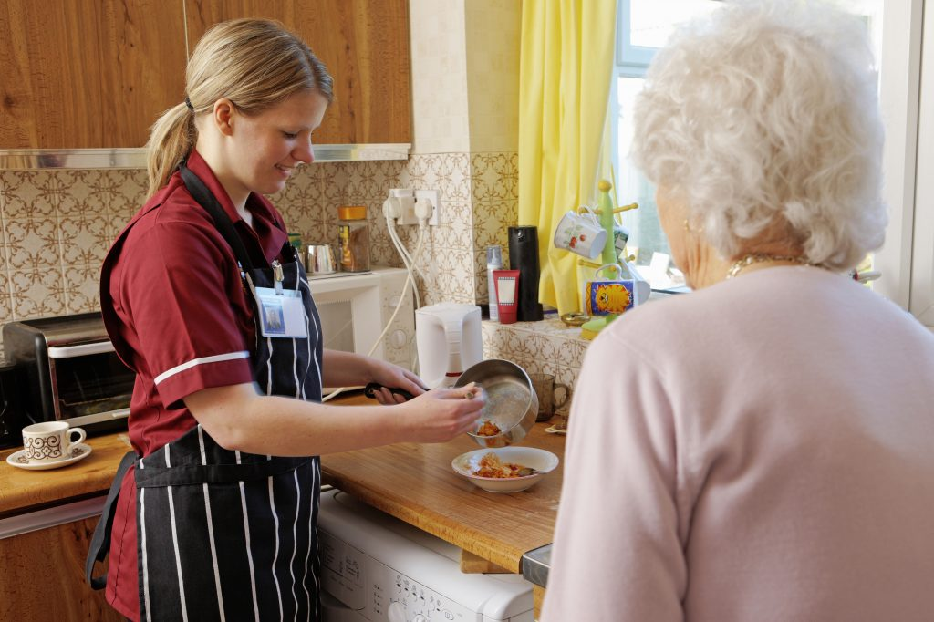 Carer helps her elderly person by cooking her a meal while doing domestic services