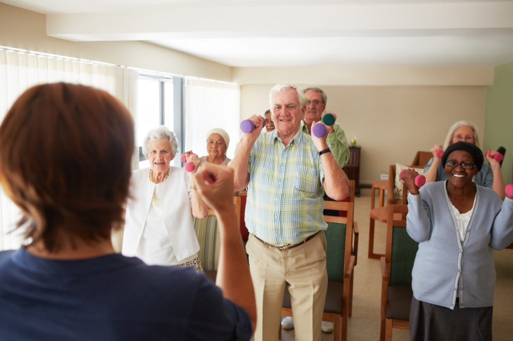 A group of seniors attending a light weight-lifting exercise class at a nursing home