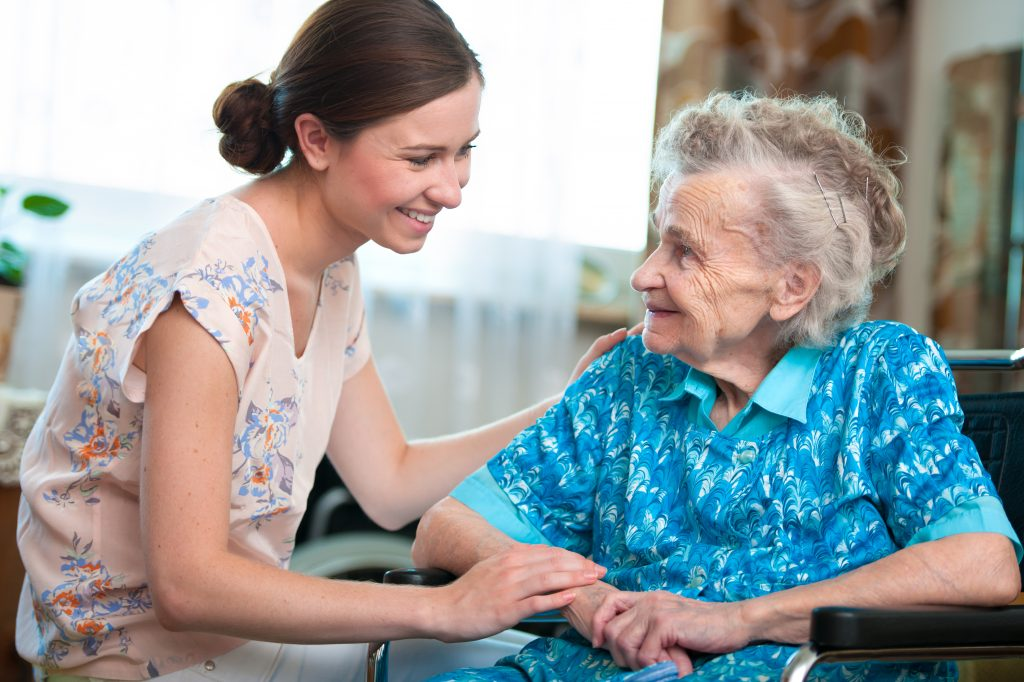 Elderly woman on wheelchair with a caregiver