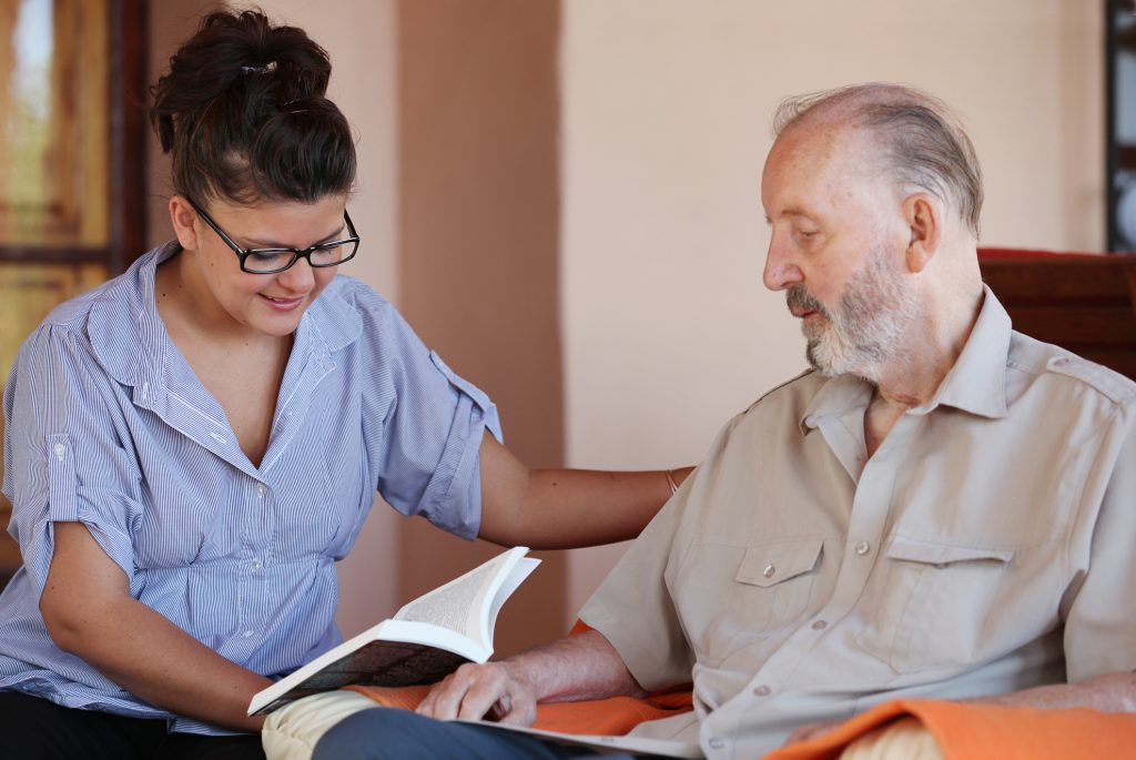 carer reading to senior while wearing a blu shirt