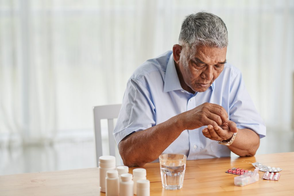 Man sitting at a table with medication a glass of water in front of him and several pills and a dosset box