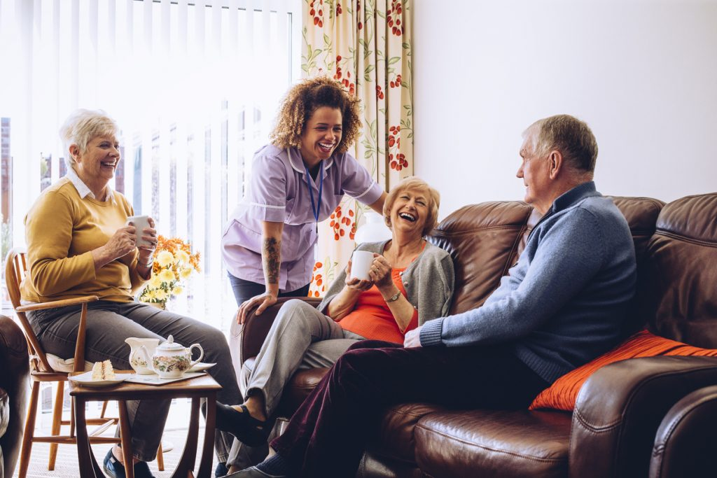 Nurse laughing with 2 people drinking tea and older man speaking