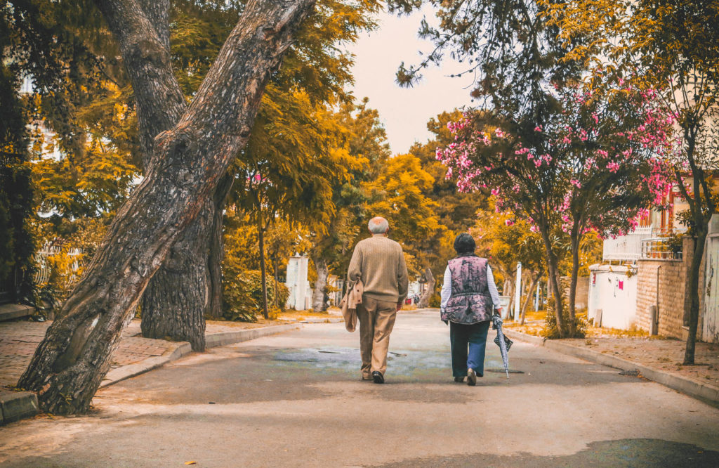 Old man and Woman waking down a road with trees in spring